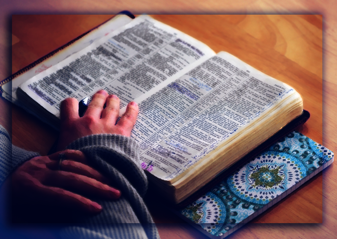 Woman's hands on Bible while studying
